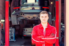 Handsome male auto mechanic standing in front of a black sedan i Royalty Free Stock Images