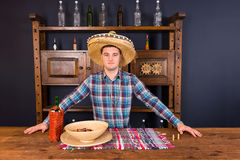 Handsome male bartender in a sombrero standing at the counter, b. Ottle of tequila and a plate with snacks on it in Mexican pub royalty free stock image