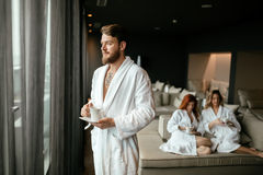 Handsome male in bathrobe drinking tea. Handsome male in bathrobe enjoying wellness weekend and drinking tea Royalty Free Stock Photos