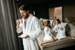 Handsome male in bathrobe drinking tea. Handsome male in bathrobe enjoying wellness weekend and drinking tea Royalty Free Stock Image