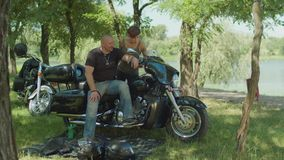 Couple of bikers discussing motorbike in nature stock footage