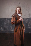 Handsome male in brown cloak, Steam punk style. Retro man portrait over grunge background. Handsome male Steam punk. Retro man portrait over grunge background Royalty Free Stock Photography