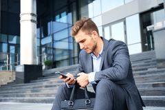 Handsome male business executive sitting on stairs outside a building. Handsome male business executive sitting on stairs outside a building Royalty Free Stock Images