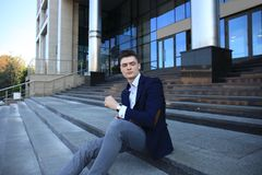 Handsome male business executive sitting on stairs outside a building. Handsome male business executive sitting on stairs outside a building Stock Image