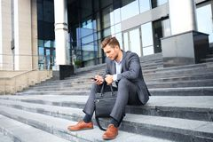 Handsome male business executive sitting on stairs outside a building. Handsome male business executive sitting on stairs outside a building Royalty Free Stock Photo