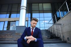 Handsome male business executive sitting on stairs outside a building. Handsome male business executive sitting on stairs outside a building Stock Photography