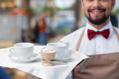 Handsome male cafe worker is serving a client Royalty Free Stock Photos