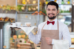 Handsome male cafe worker is serving a customer Stock Image