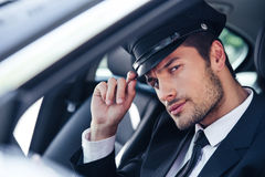 Handsome male chauffeur sitting in a car. Portrait of a handsome male chauffeur sitting in a car and making saluting gesture Royalty Free Stock Photo