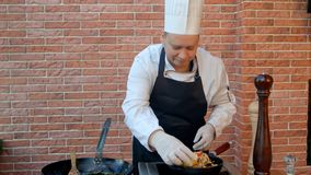 Handsome male chef dressed in white uniform decorating paella and looking at the camera smiling royalty free stock photo