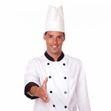 Handsome male chef with greeting gesture. Portrait of handsome 20-24 years male chef on white uniform with greeting gesture smiling at you on isolated background stock image
