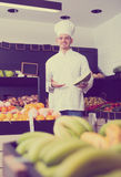Handsome male chef looking for fresh fruits Royalty Free Stock Photography