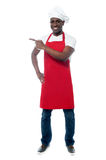 Handsome male chef showing menu. Full length portrait of chef in uniform pointing away Royalty Free Stock Photos