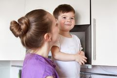 Handsome male child looks with thoughtful expression stands near kitchen furniture, being cared by affectionate young mother, curi. Ous to see something. Family Royalty Free Stock Photo