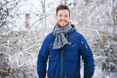 Handsome male in coat smiling at camera. Young bearded man man in warm coat smiling at camera on blurred background of snowy forest Royalty Free Stock Photography