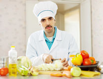 Handsome male cook does vegetarian lunch Royalty Free Stock Photo
