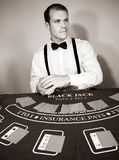 Croupier deals cards at game blackjack table. Handsome male croupier with moustache at blackjack table deals cards in casino royalty free stock photo
