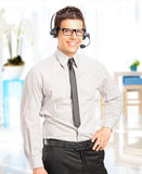 Handsome male customer operator with headset. Handsome male customer service operator with headset posing in his office Royalty Free Stock Image