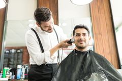 Customer Smiling While Barber Trimming His Hair In Shop. Handsome male customer smiling while barber trimming his hair in shop Stock Photos
