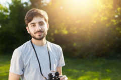 Handsome male with dark hair, big eyes and beard having walk at forest holding binoculars on his neck trying to discover something Stock Image