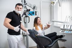 Handsome male dentist with attractive female patient after treatment in modern dental clinic. Doctor and patient are looking to the camera and showing thumbs Royalty Free Stock Photo