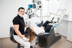 Handsome male dentist with beautiful female patient during treatment in modern dental clinic. Doctor looking to the camera. Dentistry. Stomatology equipment Stock Image