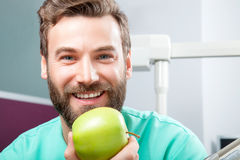 Handsome male doctor with beard smiling and holding green apple. Portrait of young handsome male doctor with beard smiling with perfect straight white teeth Royalty Free Stock Image
