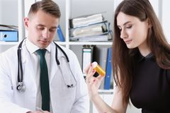 Handsome male doctor explain prescription while. Patient hand hold jar of pills. Panacea and life save prescribe antidepressant legal drug store vitamin aid Royalty Free Stock Images