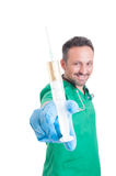 Handsome male doctor holding a syringe. To the camera on white studio background Stock Photos