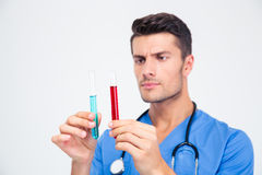 Handsome male doctor holding tube with liquid. Portrait of a handsome male doctor holding tube with liquid isolated on a white background Royalty Free Stock Image