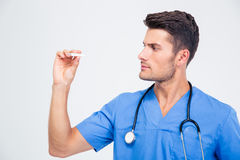 Handsome male doctor looking on thermometer. Portrait of a handsome male doctor looking on thermometer isolated on a white background Stock Images