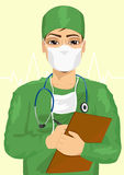 Handsome male doctor or nurse in face mask taking notes Stock Image