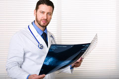 Handsome male doctor portrait holding patients x-ray. Handsome male doctor portrait with stethoscope on his neck standing while holding patients x-ray; looking Royalty Free Stock Photos
