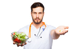Handsome male doctor showing salad and pills Stock Photography