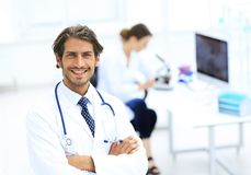 Handsome male doctor smiling with arms crossed on chest portrait. Successful happy smiling male doctor with phonendoscope Royalty Free Stock Images