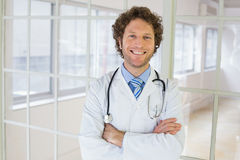 Handsome male doctor standing with arms crossed. Portrait of a happy handsome male doctor standing with arms crossed in the hospital Stock Images