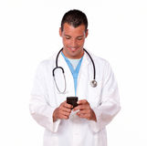Handsome male doctor texting a message. Portrait of a handsome 20-24 years male doctor texting a message with his cellphone while standing on isolated background Stock Photos