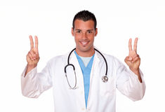 Handsome male doctor with two winning sign Royalty Free Stock Photos