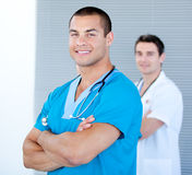 Handsome male doctors in a row with folded arms Royalty Free Stock Images