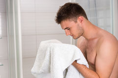 Handsome male dries his face with a clean towel. After washing procedures in the modern tiled bathroom Royalty Free Stock Image