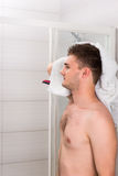 Handsome male dries his wet hair with a clean towel. After washing procedures in the modern tiled bathroom Royalty Free Stock Images