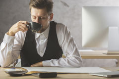 Handsome male drinking coffee at workplace Royalty Free Stock Image