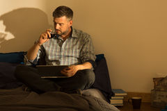 Handsome male drinking wine. Picture of handsome male drinking wine in bed royalty free stock photography