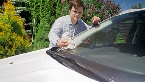 Handsome young male driver cleaning his car windscreen with rag. Handsome male driver cleaning his car windscreen with rag Royalty Free Stock Photo