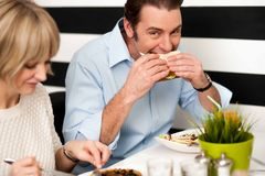 Handsome male enjoying his delicious sandwich Stock Photo