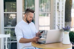 A handsome male European is sitting outside in a cafe, working on a laptop, making purchases through the Internet royalty free stock image