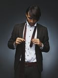Handsome male fashion model getting dressed Stock Images