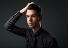 Handsome male fashion model with hand in hair Stock Image