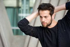 Handsome male fashion model posing with hands behind head. Close up portrait of a handsome male fashion model posing with hands behind head Royalty Free Stock Images
