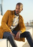 Handsome male fashion model sitting outdoors Stock Photo